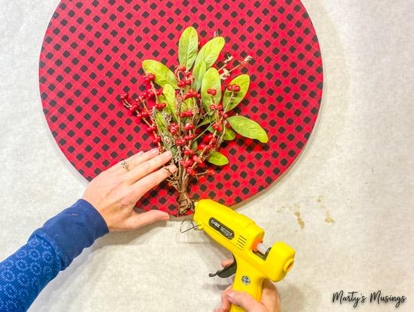hot glue floral stems to buffalo plaid hoop wreath