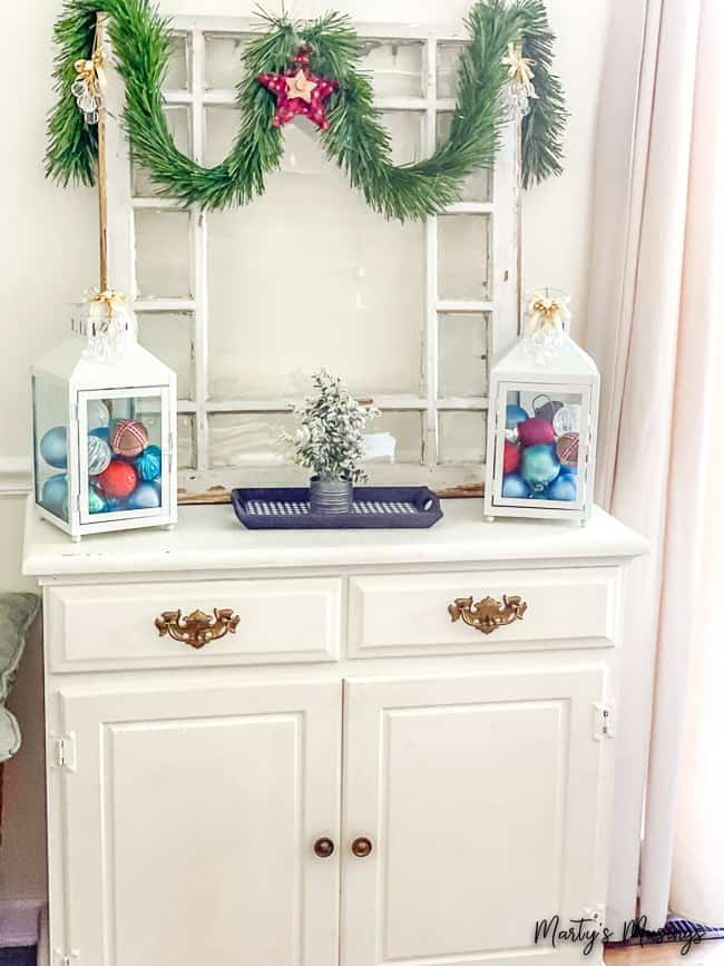 white hutch with lanterns filled with red, blue and white ornaments and greenery hung from an old window