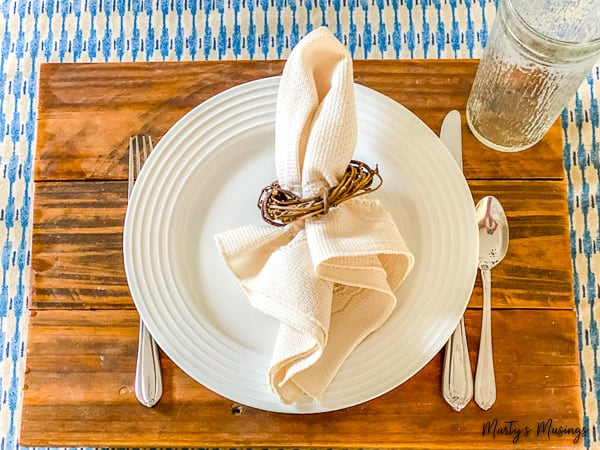 Rustic wood charger with white plates and blue tablecloth