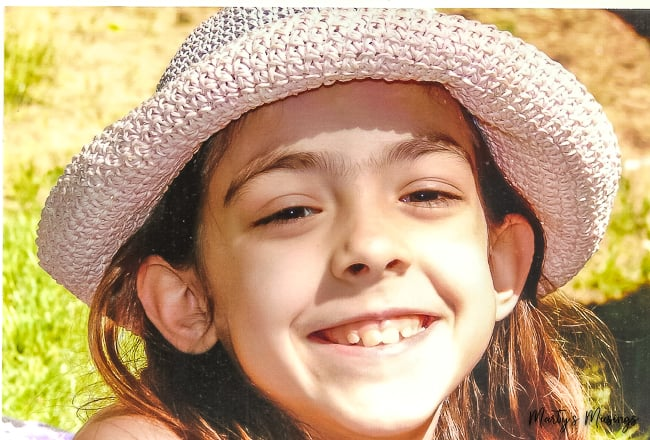 young girl in pink hat outside