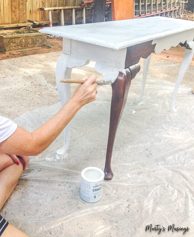 Sofa table being painted with white chalk paint outdoors