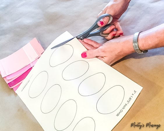 cutting out ovals next to pink paint chips