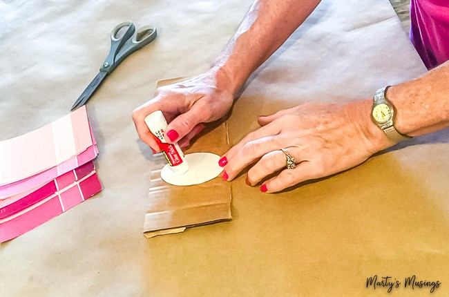 glueing oval onto cardboard with pink paint chips