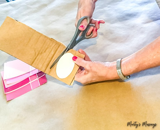 cut out oval from heavy cardboard with pink paint chips on the counter