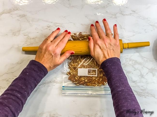 woman using rolling pin to smash pecans