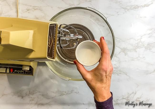 woman pouring vinegar into a vintage mixer