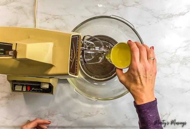 woman pouring egg whites into vintage mixer