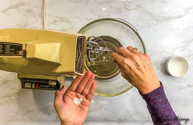woman sprinkling salt into vintage mixer