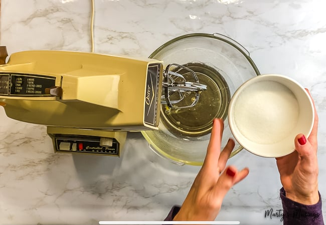 woman pouring sugar into vintage mixing bowl