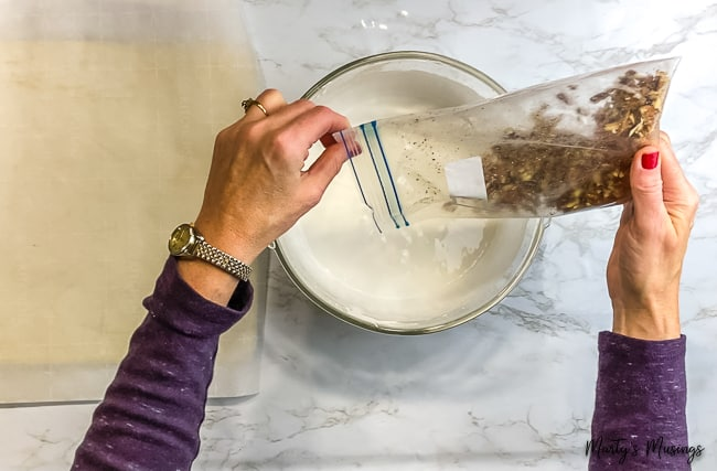 woman pouring crushed nuts into meringue mixture