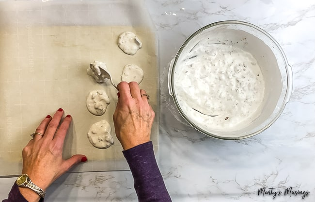 woman placing Easter Resurrection Cookies onto parchment paper